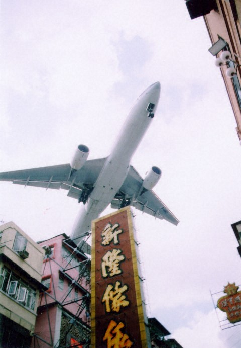 Airliner landing at Kai Tak, flying over residential area - Ghost Airports