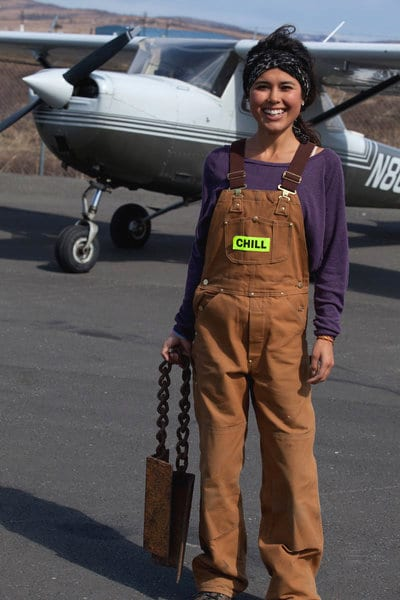 Ariel Tweto standing on a runway in front a tailldragger airplane.
