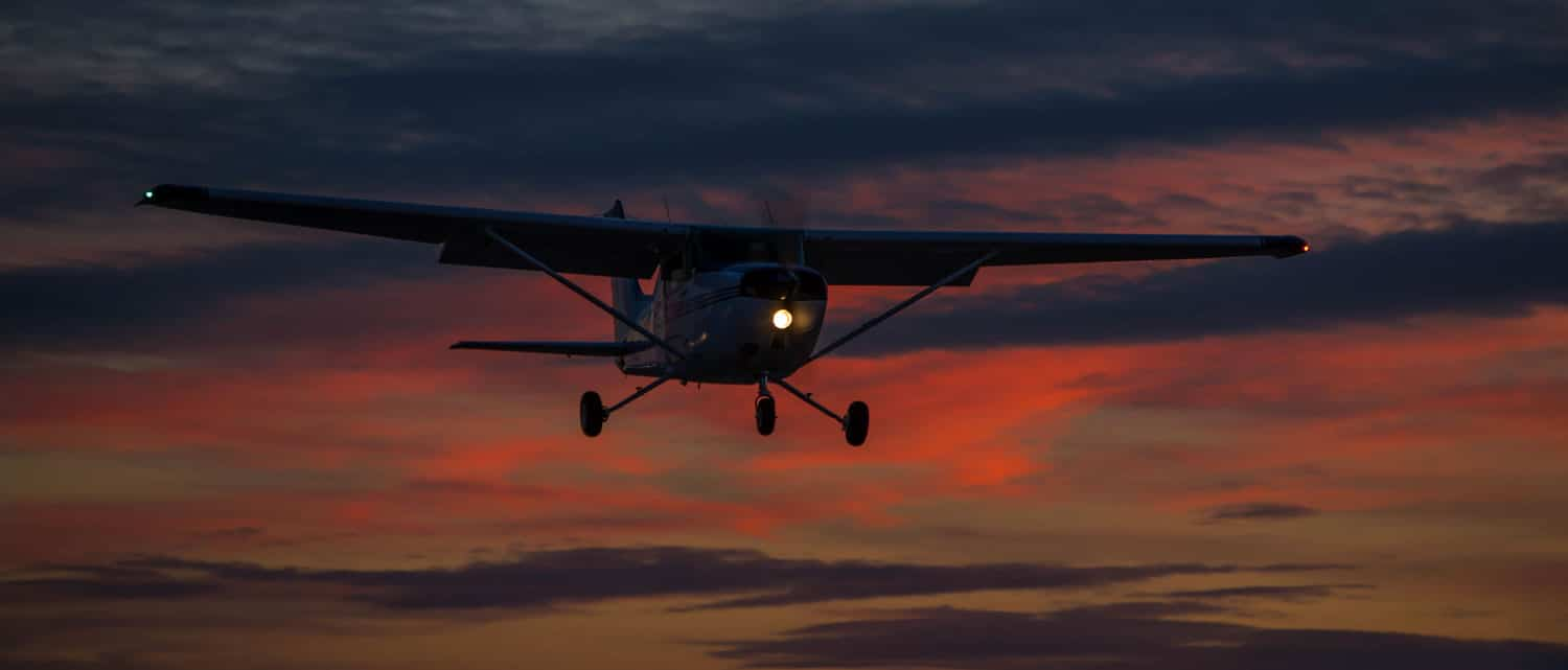 A small Cessna aircraft enjoying some night flying.