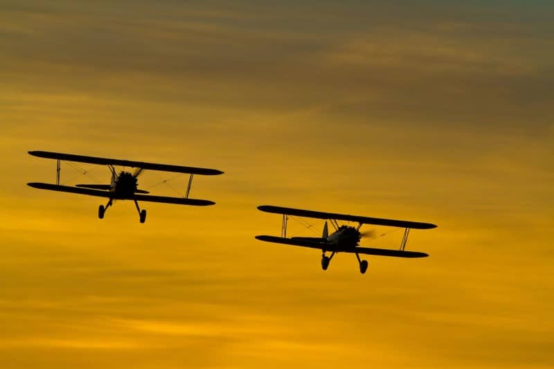 Biplanes flying against a sunset. - 2012 Reno Air Races