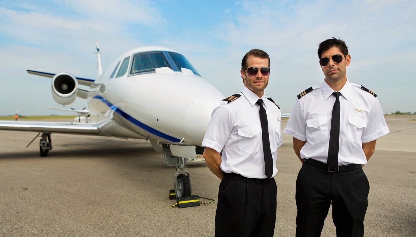 Portrait of confident pilots standing in front of private jet - The Right Pilot Seat For You