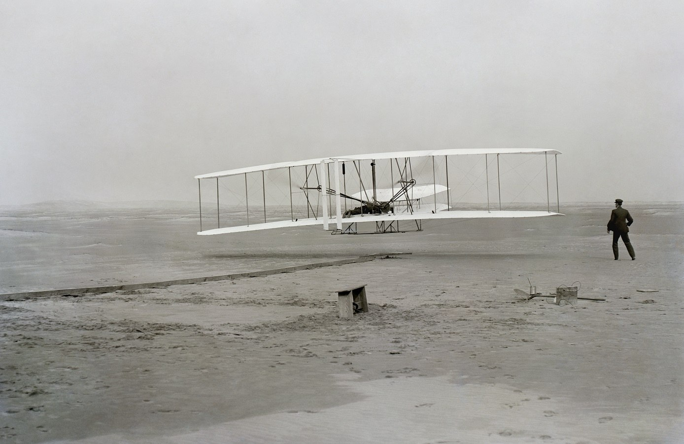 The historic photo captured by John T. Daniels of the Wright Brothers powered first flight - First Flight: the Wright Brothers