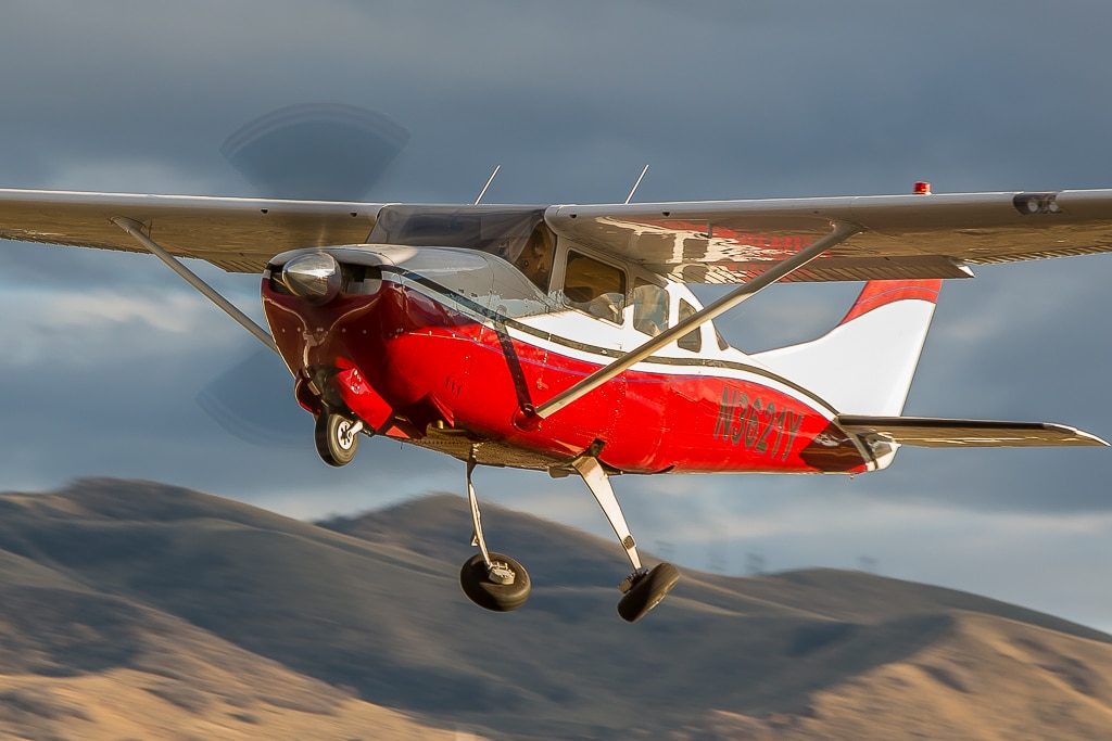 A Cessna 210 Centurion retracting its landing gears after take off