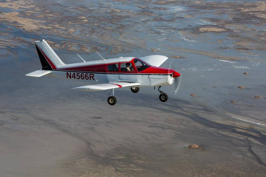 A Piper Cherokee 140 in the air over the Great Salt Lake