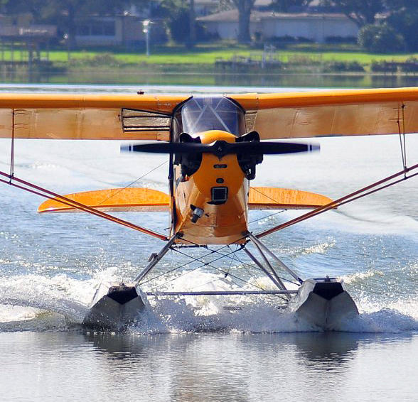 A seaplane taking off from a small lake.