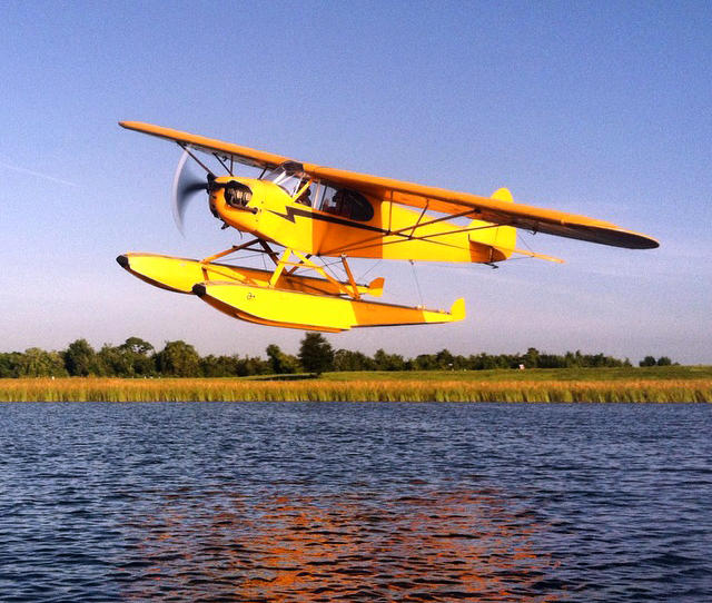 A Piper J3 Cub Seaplane with floats flying over a lake.