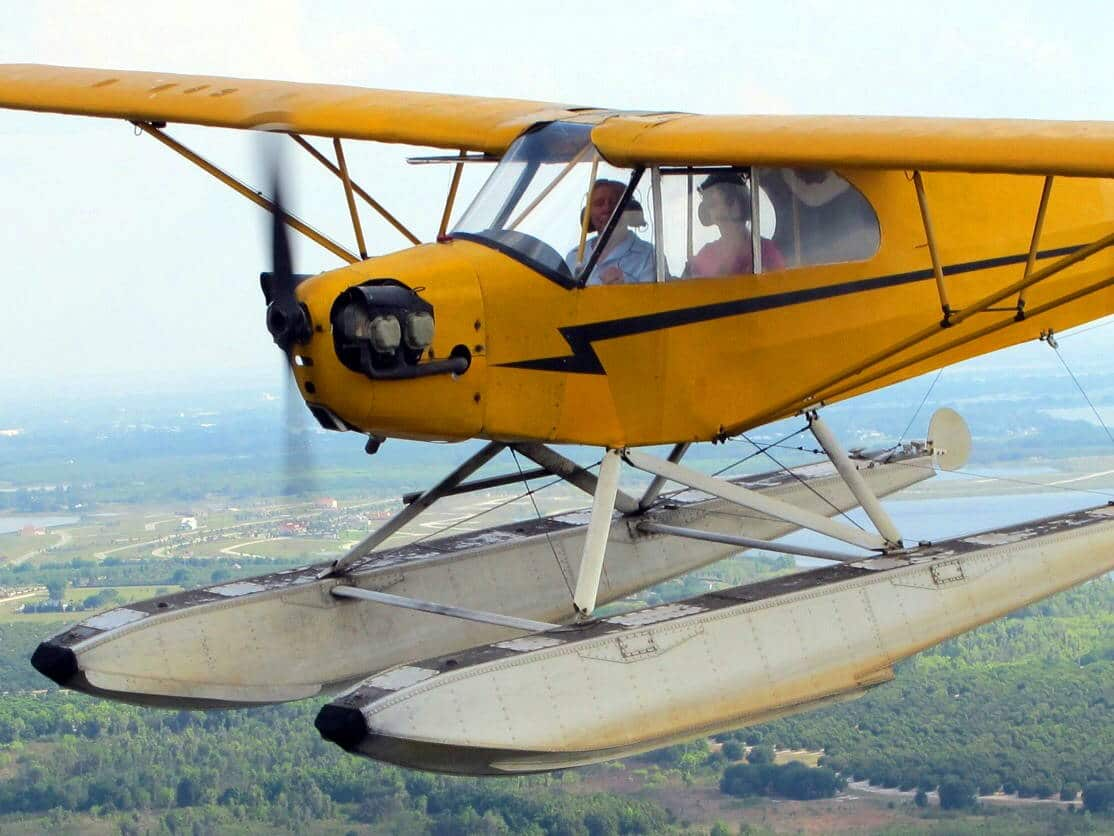 A Piper J3 Cub seaplane in flight over Florida.