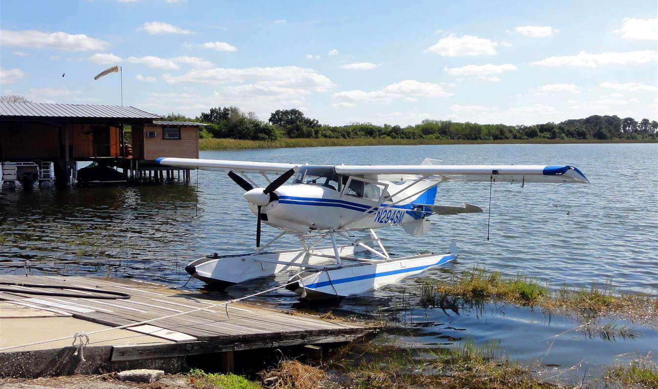 A seaplane pulled up to a small dock on a lake.
