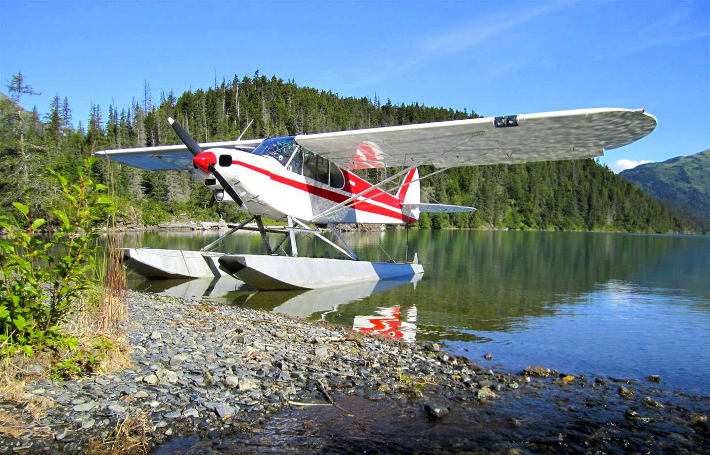 A seaplane docked in a small Alaskan glacial lake.