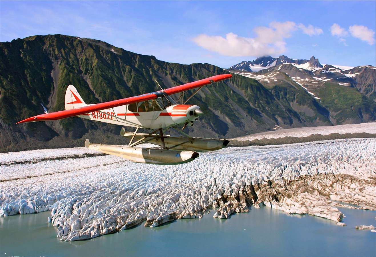 A seaplane flying over a glacial lake in Alaska.