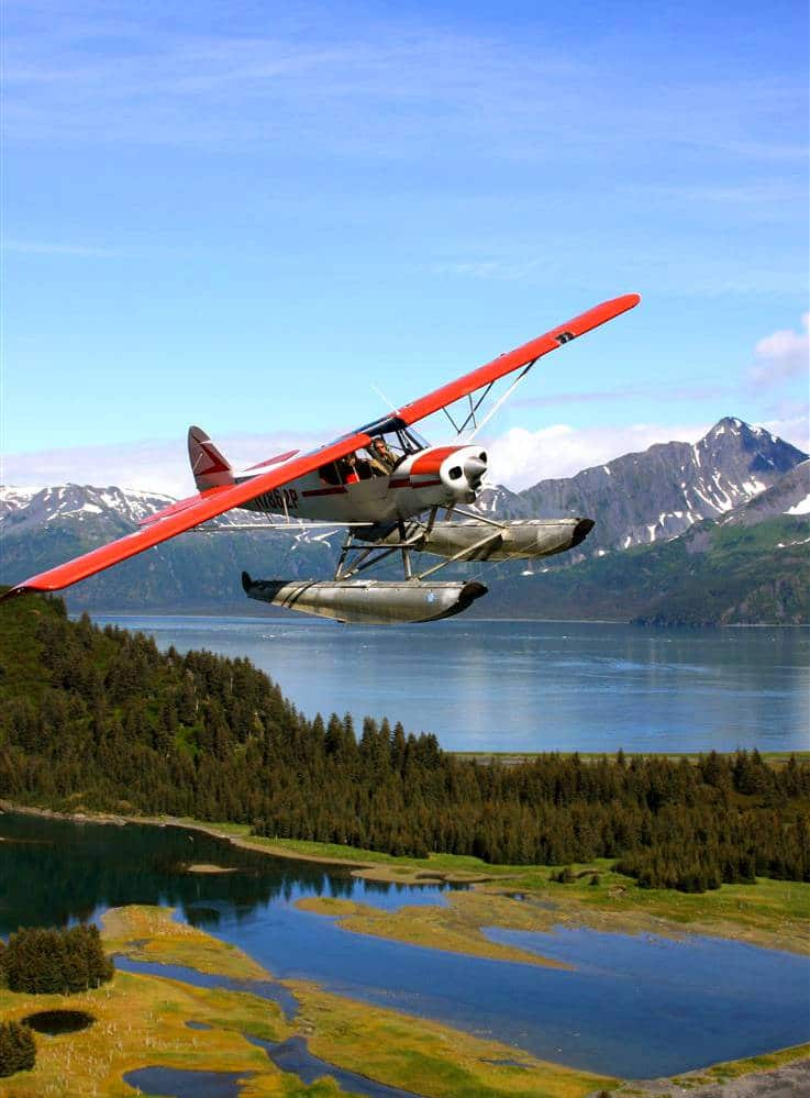 A seaplane flying over the Alaskan wilderness.