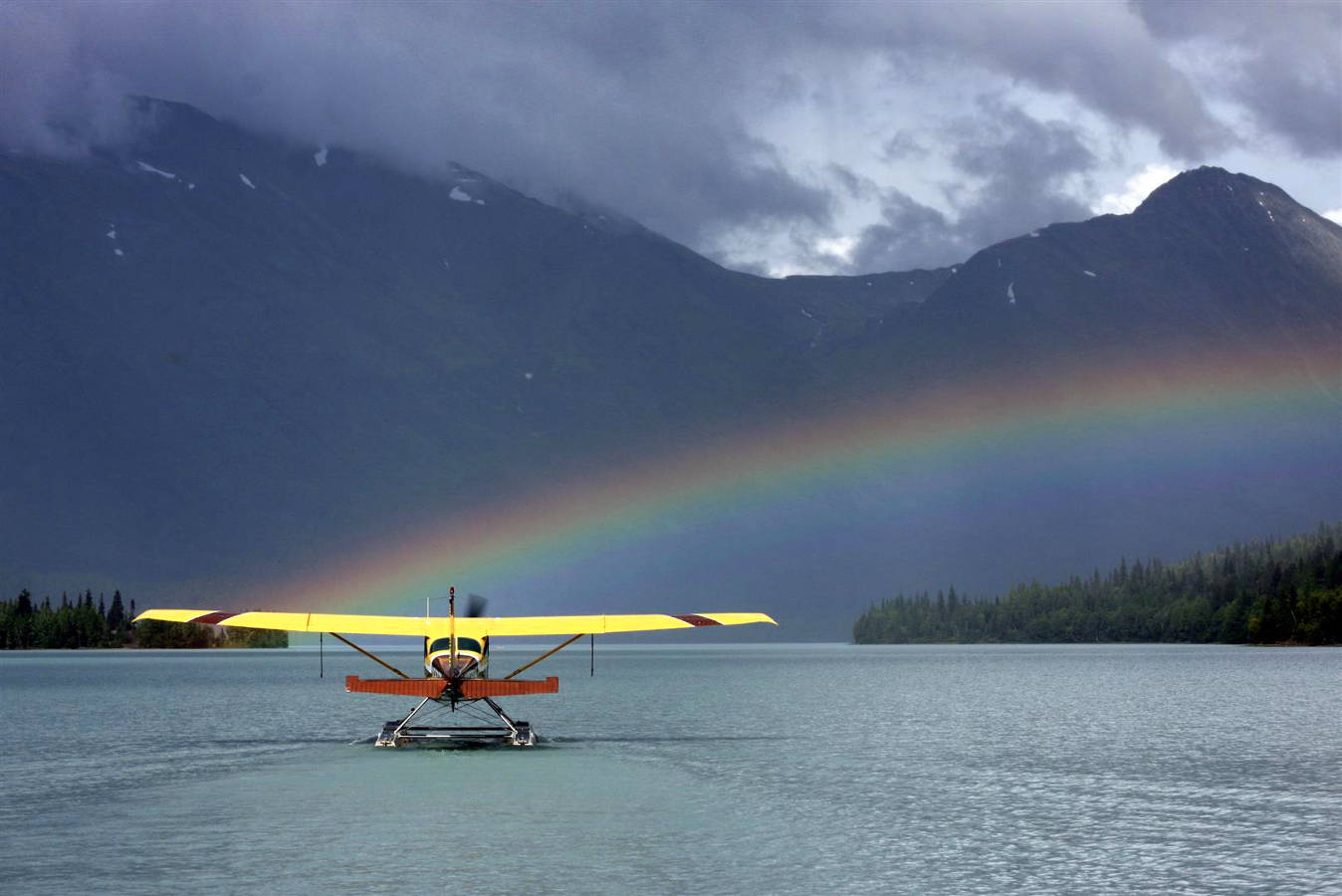 A seaplane on a beautiful Alaskan lake with a rainbow.