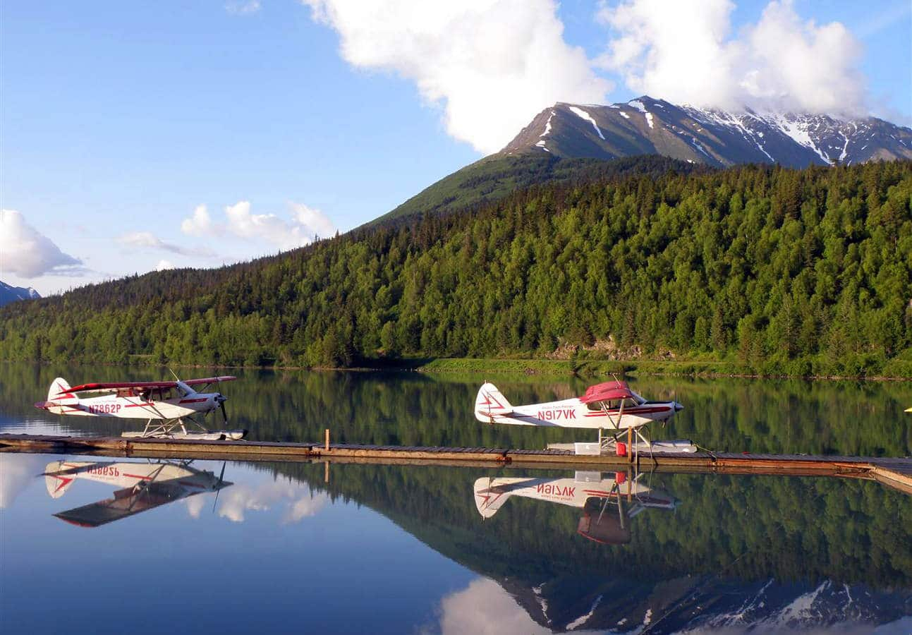 Seaplanes parked at a dock on an Alaskan lake.
