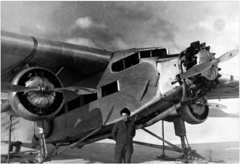 Noel Wien standing next to a Ford Trimotor plane.