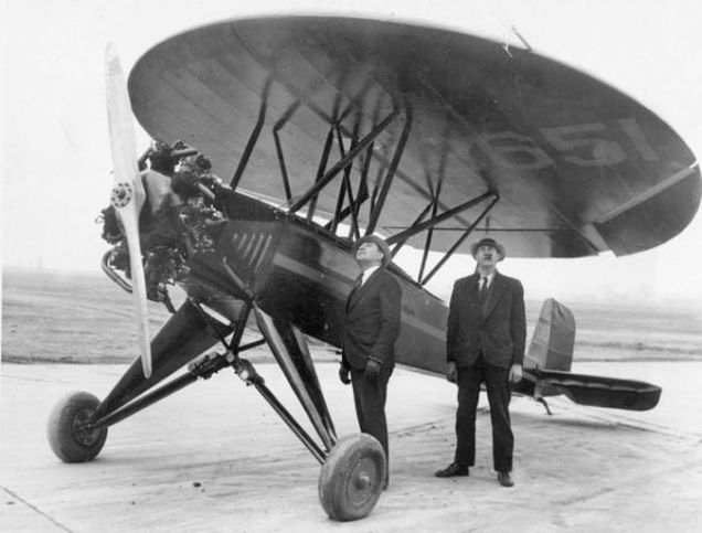 A photo of two men looking over the strange aircraft known as the Nemeth Parasol.