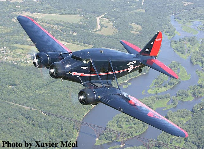 Restored Stinson Model A aircraft in flight.