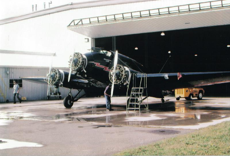 A Stinson Model A aircraft undergoing restoration work, with the propellers being hung.