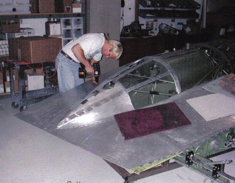 A man working on restoring the metal frame on a Stinson Model A aircraft.