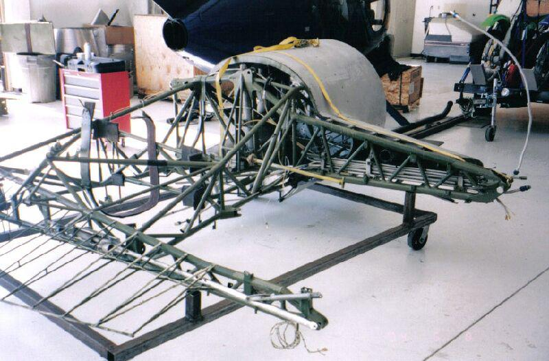 Working to restore the metal frame on a Stinson Model A aircraft.