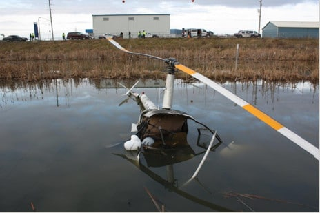 A helicopter crashed in a marsh due to a carburetor icing problem.