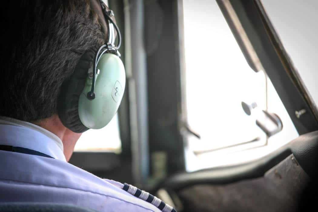 A career pilot wearing a headset in the cockpit of an aircraft.