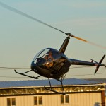 Pilot flying a helicopter around wires and electrical transmission towers.