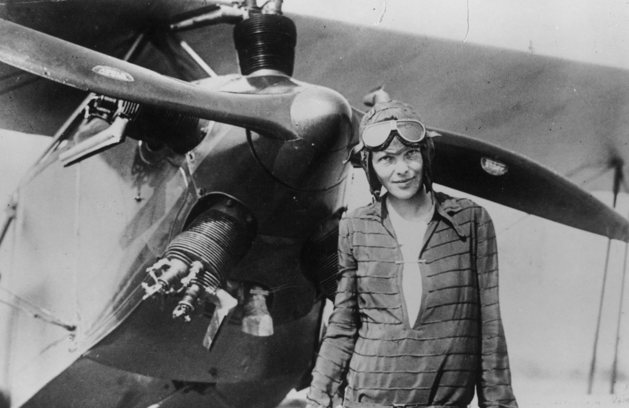 Amelia Earhart stands next to her Kinner Airster - What Happened to Amelia Earhart