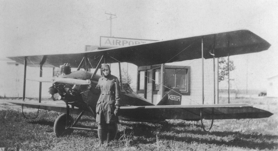 Amelia Earhart standing next to her Kinner Airster.