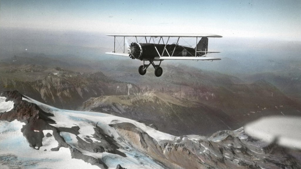 A Boeing Model 40A flying over a mountain range in the 1930s