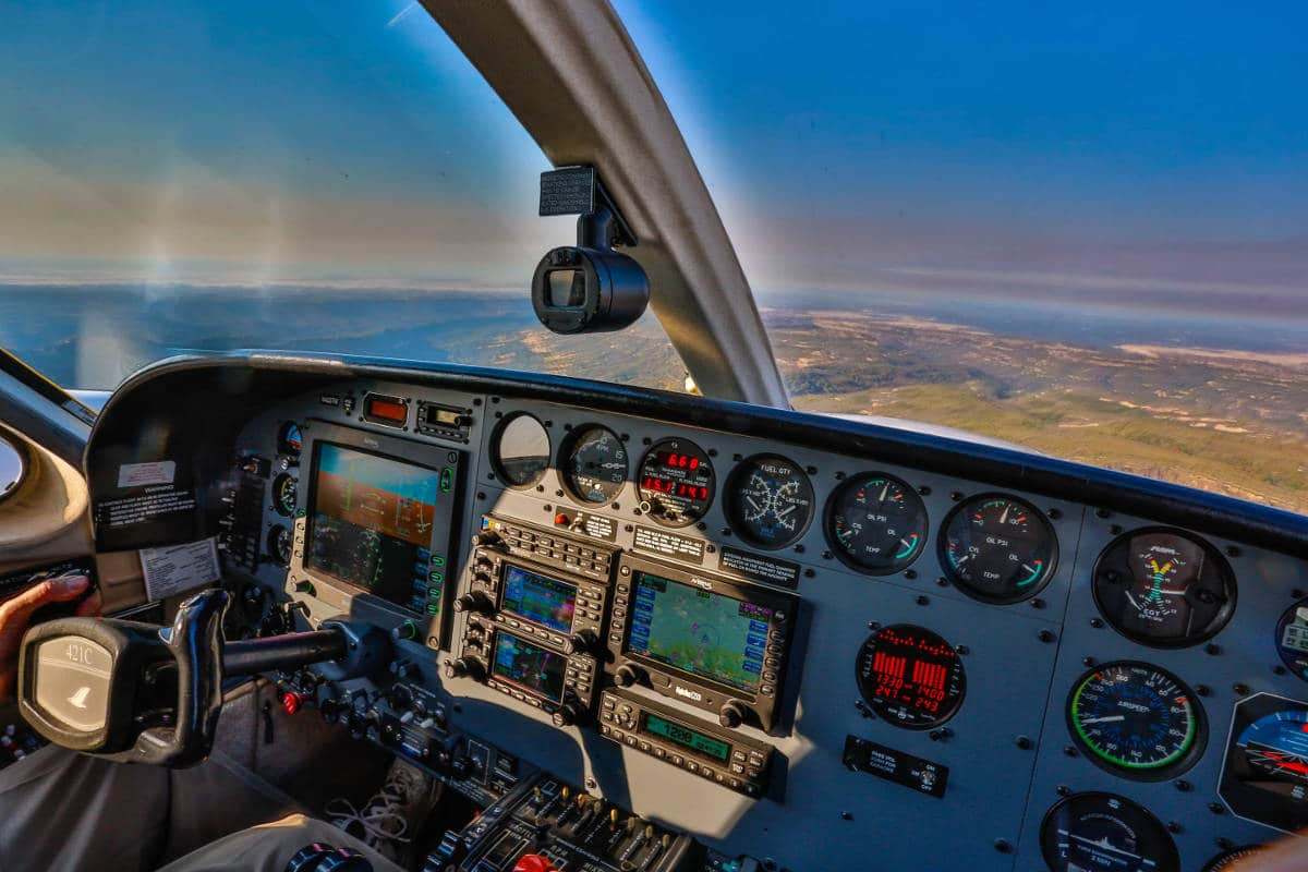 The view, including the instrument panel, from a Cessna 421 Golden Eagle in flight.