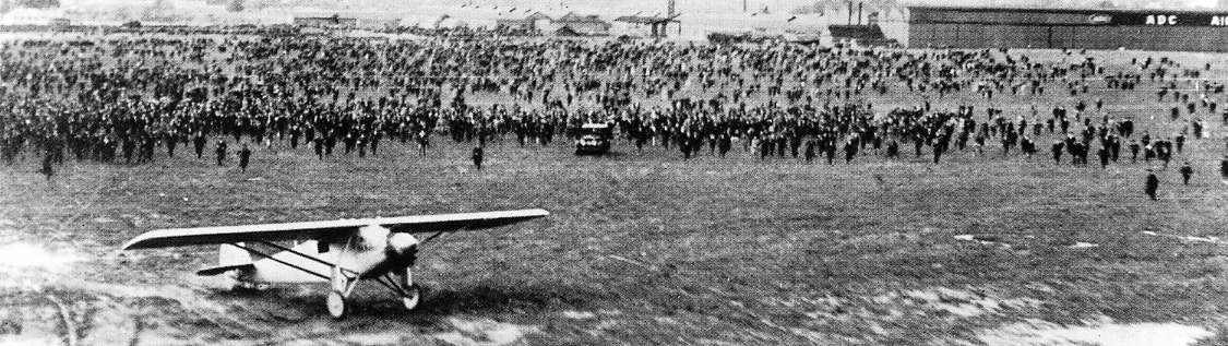 Crowds race to meet Charles Lindbergh after he lands the Spirit of St. Louis in England.