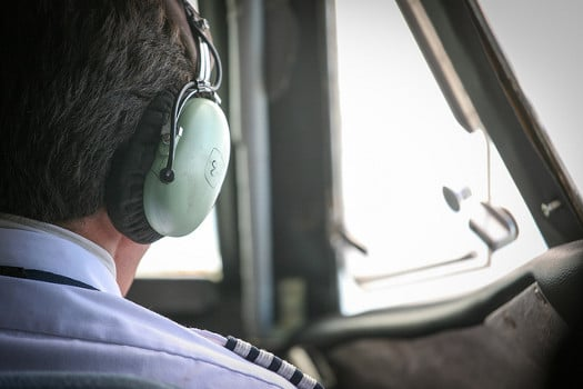 Airline pilot with a headset, in the cockpit - Are All Airline Pilot Training Schools the Same?