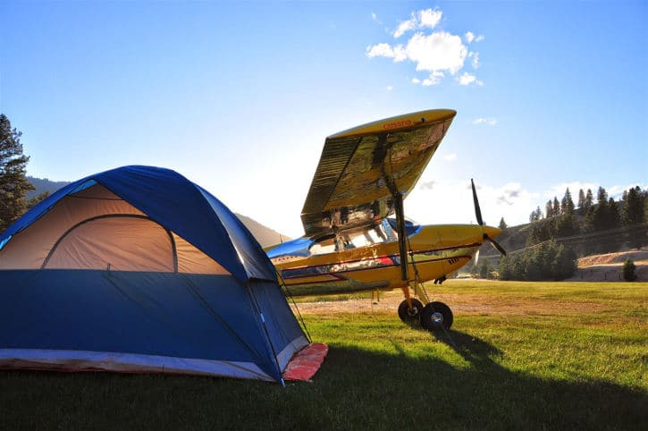 A Cessna 180 Skywagon against a sunrise, with a camping tent
