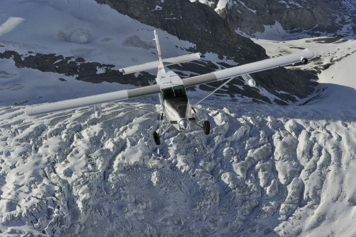 A Pilatus PC-6 Porter flying over the snow
