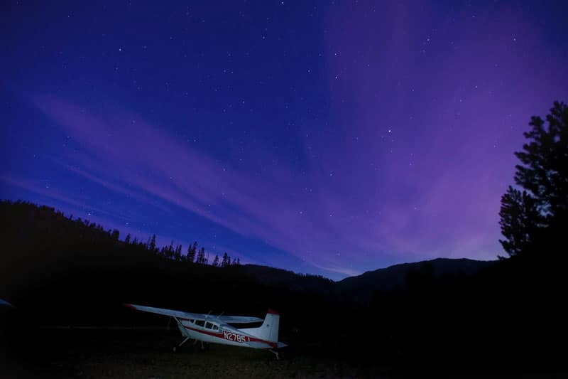 A Cessna 185 Skywagon at a backcountry airstrip with the night sky