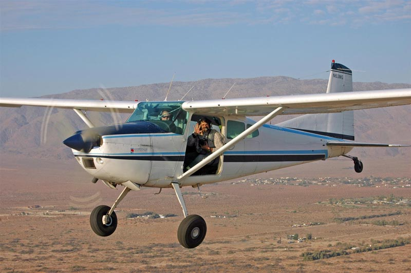 A Cessna 185 Skywagon flying with the door off to take photographs
