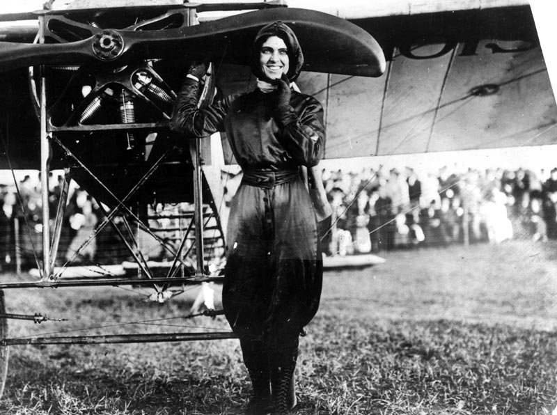 Female pilot Harriet Quimby standing next to her aircraft
