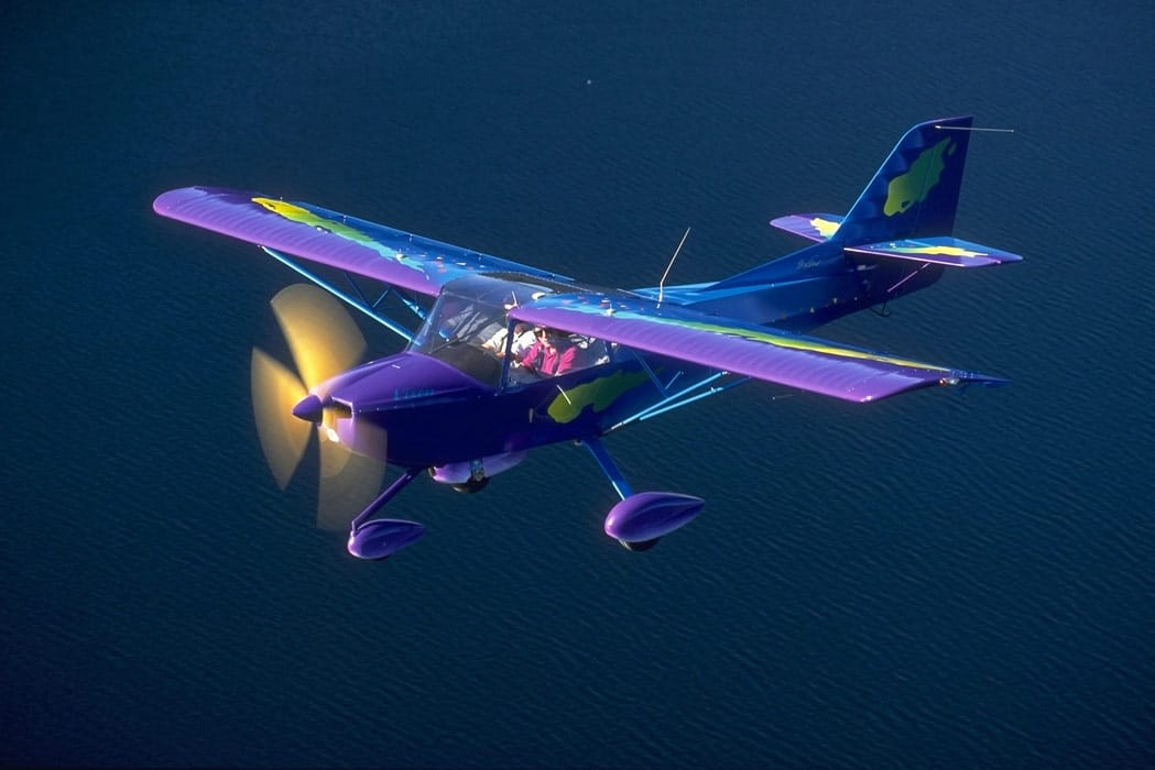 A Kitfox experimental aircraft flying over a lake