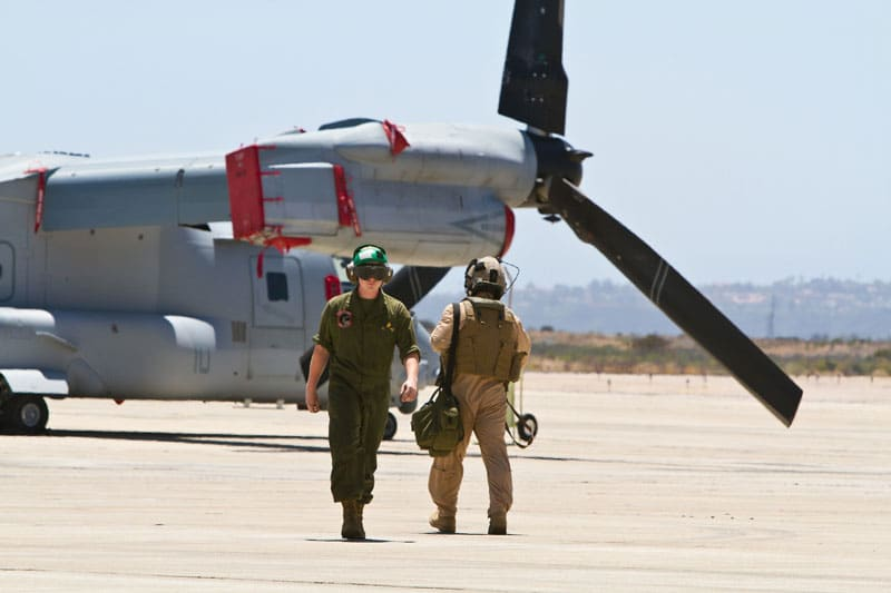 Military pilots with an Osprey aircraft in the backgorund