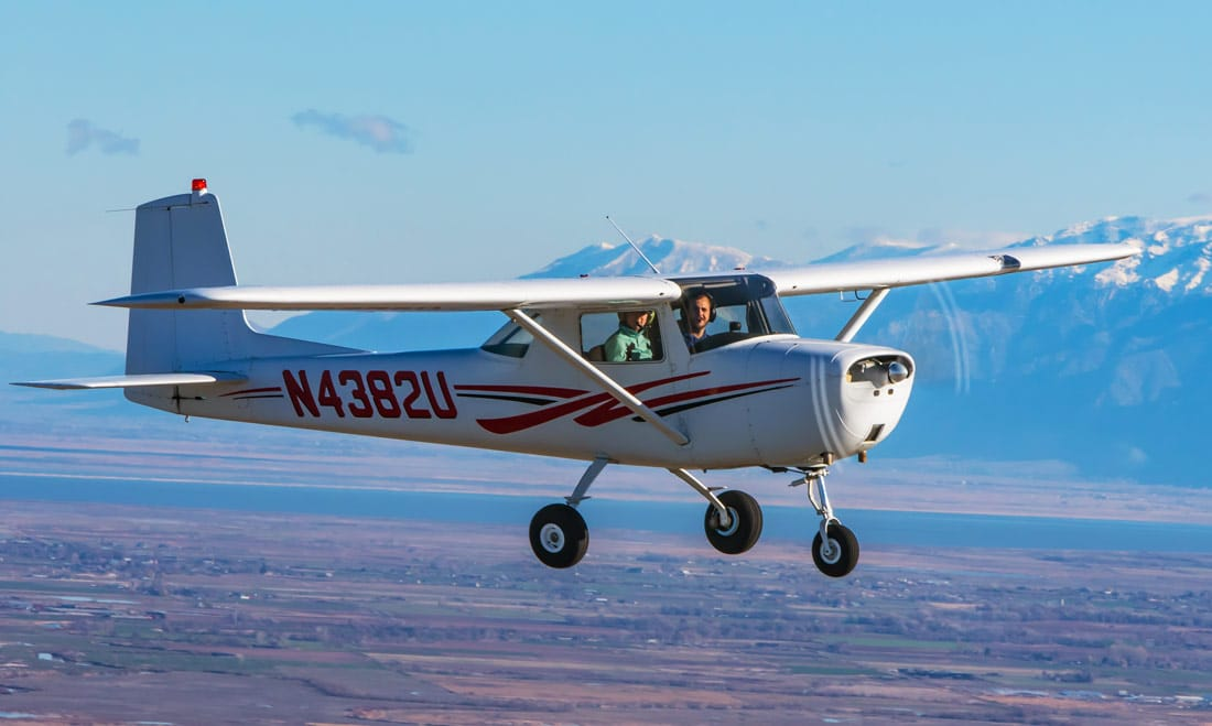A Cessna 150 flying over the valley - All About the FAA Wings Program