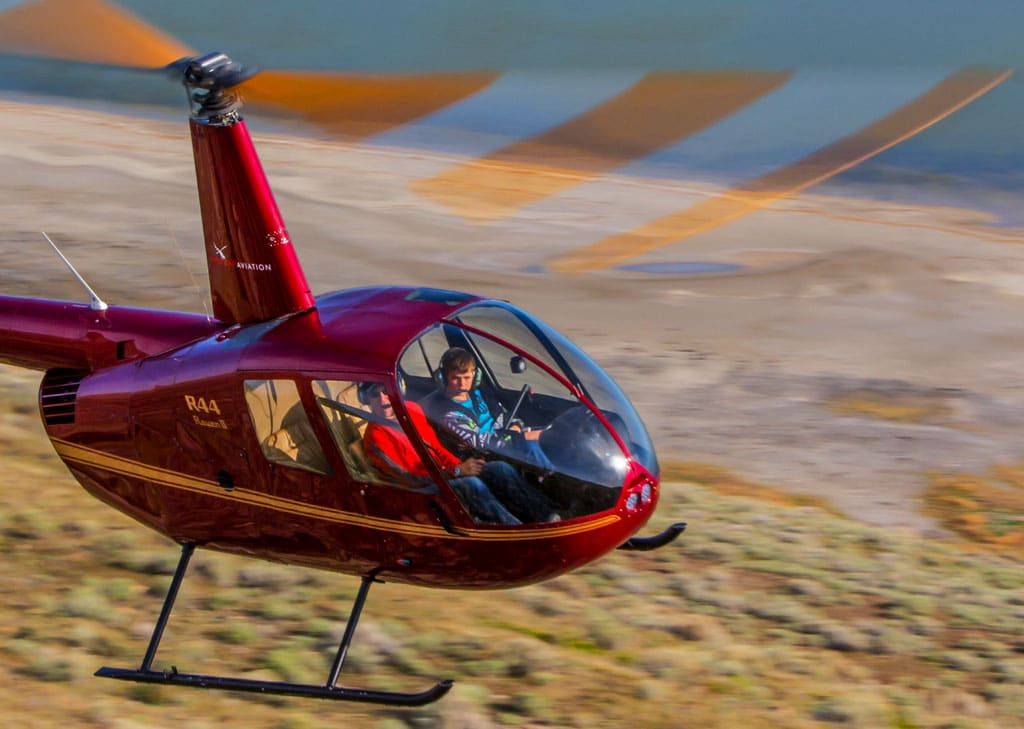 Robinson R44 Helicopter in flight by the shore of a lake