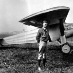 Charles Lindbergh standing next to the Spirit of St. Louis