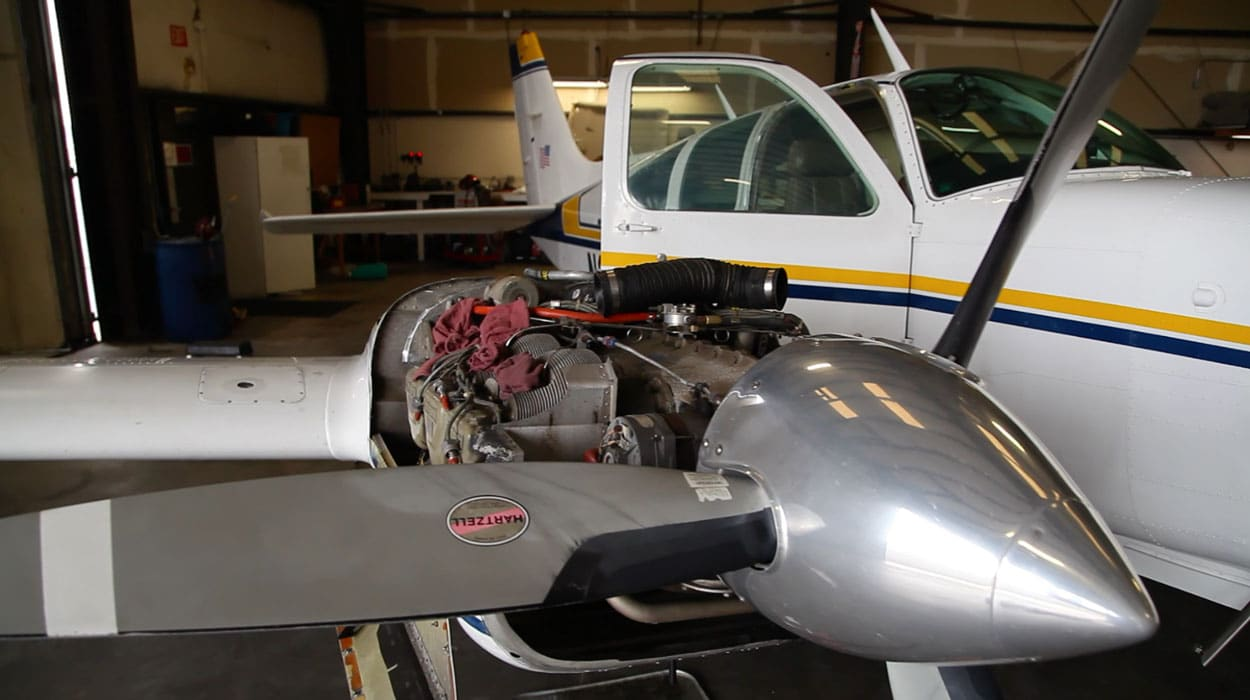 Twin engine aircraft being worked on by in an aviation mechanics shop
