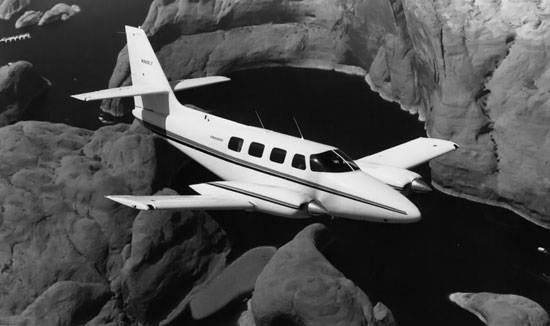 Cessna T303 Crusader in flight over redrock and water