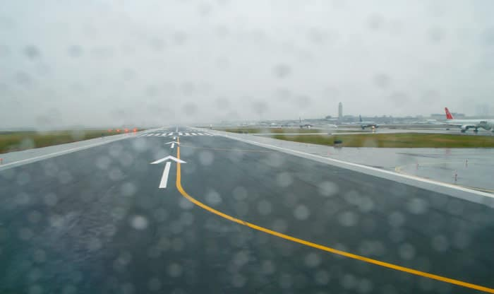 Raining at the airport, which can lead to contaminated runways