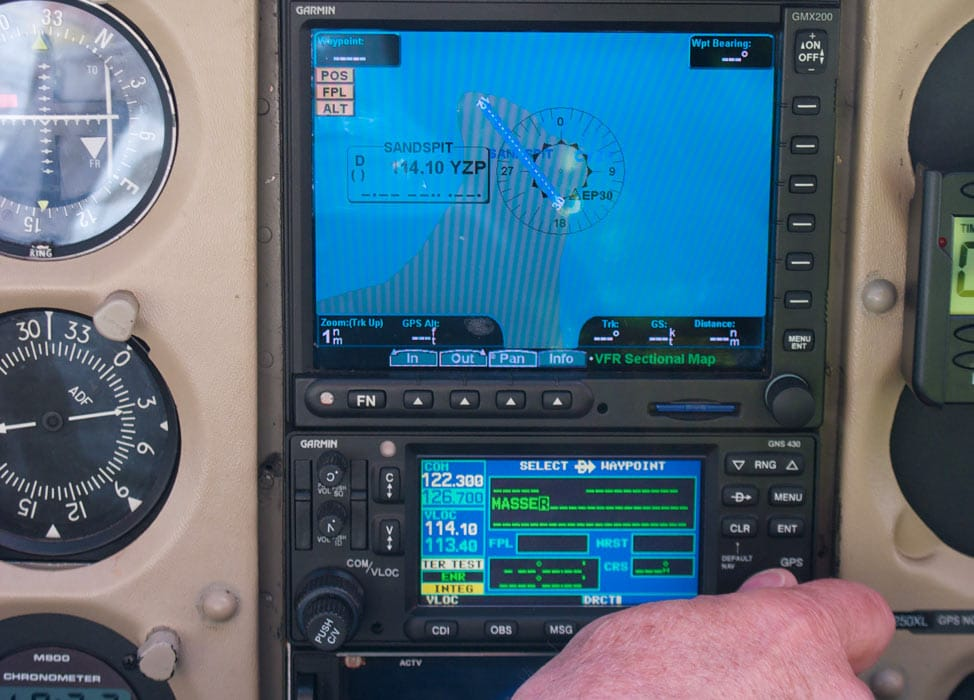 Man adjusting GPS input on an aircraft instrument panel - FAA Issues Flight Advisories for GPS Interference Testing