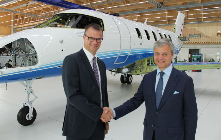 The first production model Pilatus PC-24 going through a wing fuselage marriage procedure, with PlaneSense CEO and PC-24 VP.