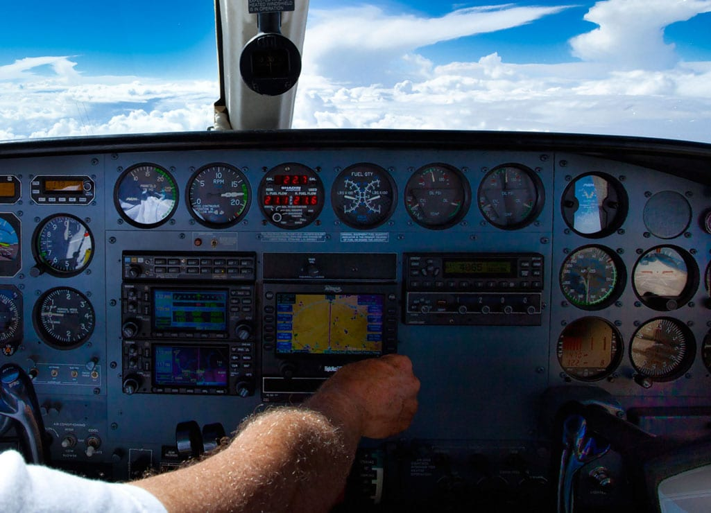 Pilot adjusting GPS on instrument panel of Cessna 421 - FAA Schedules 2017 GPS Interference Testing advisories