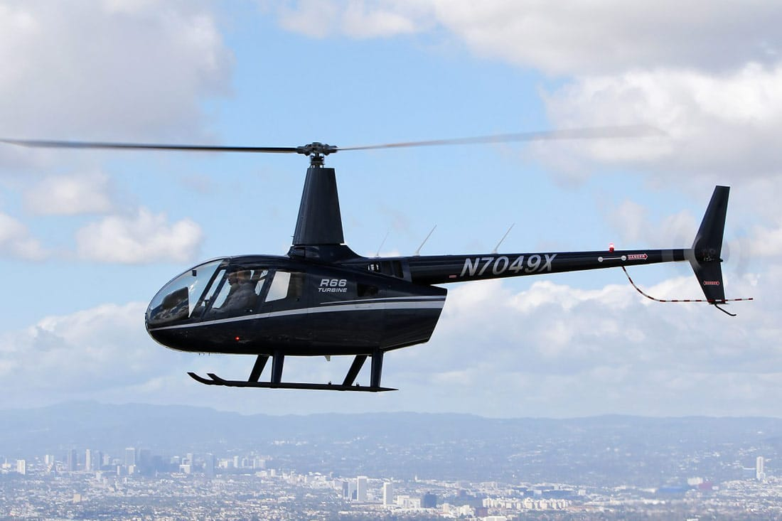 An R66 Helicopter in flight, in midnight blue