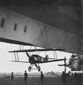 sopwith camel strung up under an airship